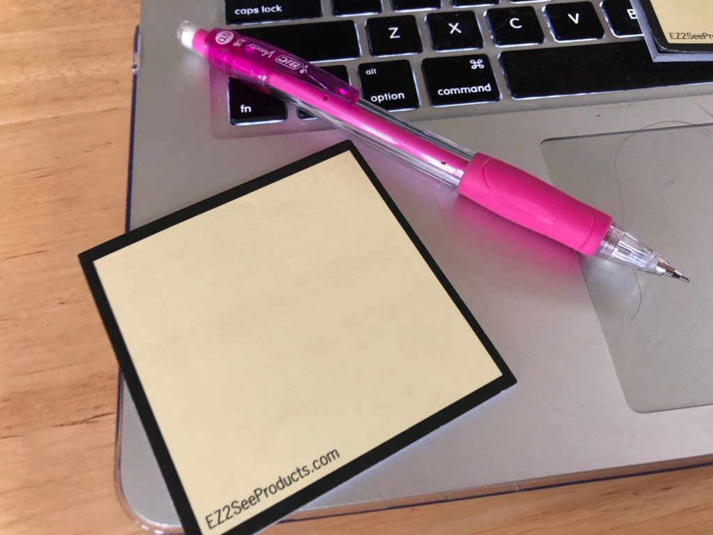 Image of a EZ2See Sticky Note on a computer keyboard, with a pink pen along side it.